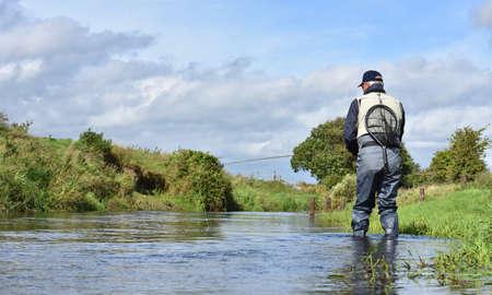 botas altas: Vista posterior de la pesca con mosca pescador en el río