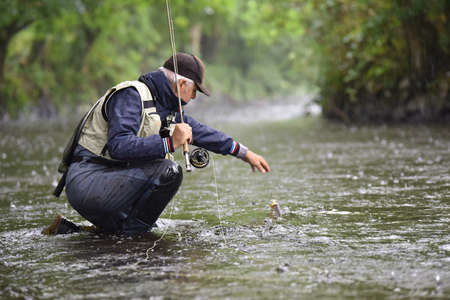 雨の中、川でフライ漁師キャッチ マス