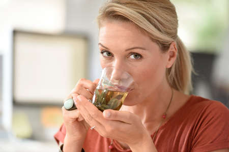 Attractive woman designer drinking tea in office