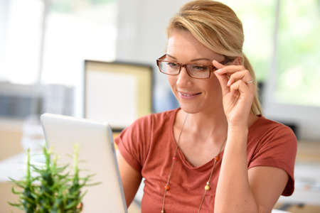 homeoffice: Attractive home-office woman working on digital tablet Stock Photo