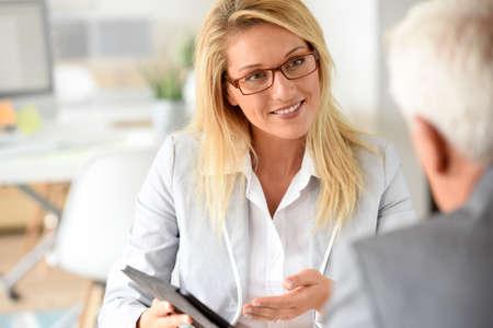 Zakenvrouw met klant in zakelijke bijeenkomst Stockfoto