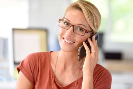 homeoffice: Attractive blond middle-aged woman talking on phone