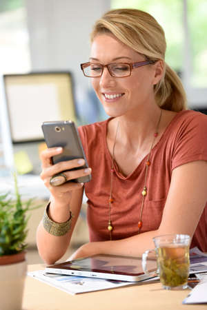 homeoffice: Woman at home-office using smartphone