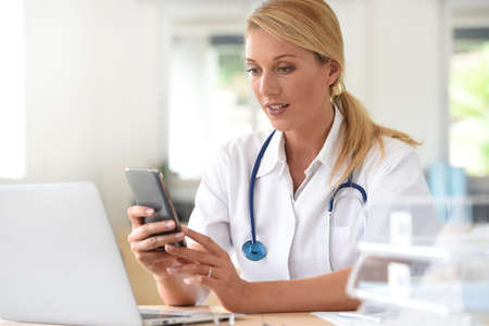 a lady doctor: Portrait of nurse in office using smartphone
