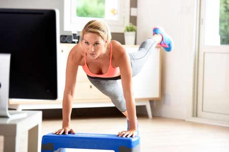 Chica de gimnasio haciendo ejercicios delante de la TV