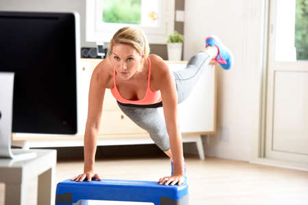 Fitness meisje doet oefeningen voor de tv Stockfoto