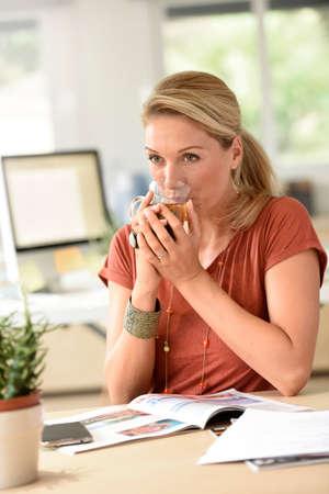 woman drinking tea: Attractive woman designer drinking tea in office