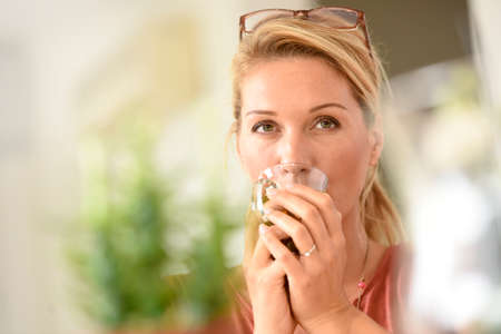 middleaged: Smiling attractive blond woman drinking hot tea