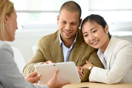 consultant: Cheerful married couple meeting financial adviser Stock Photo