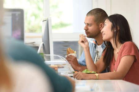 Office-workers having lunch in office in front of desktop