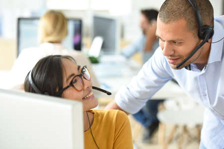 servicio al cliente: Sonriendo ayudante de la oficina del cliente con el gerente en la oficina Foto de archivo