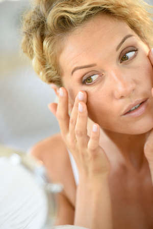 beautycare: Middle-aged blond woman putting cosmetics on