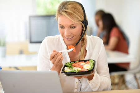 Drukke customer service manager eten van de lunch in het kantoor Stockfoto