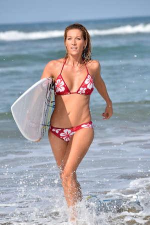 Surfer ragazza che corre fuori dall'acqua Archivio Fotografico