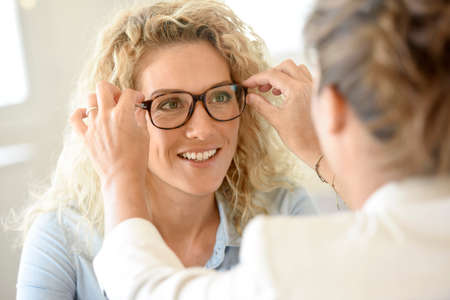 woman  glasses: Blond woman at the optical shop, trying eyeglasses on