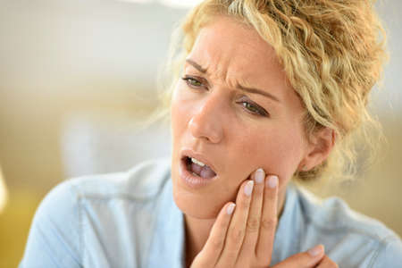 Middle-aged woman suffering toothache 스톡 콘텐츠