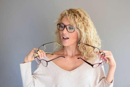 다른 안경 사이에서 선택하는 곱슬 머리를 가진 금발의 여자