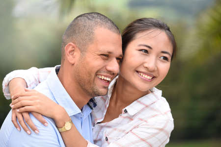 each: Cheerful ethnic couple embracing each other