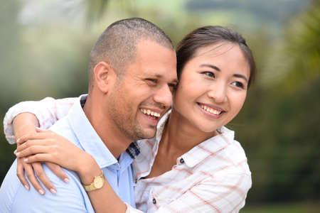 ethnic couple: Cheerful ethnic couple embracing each other