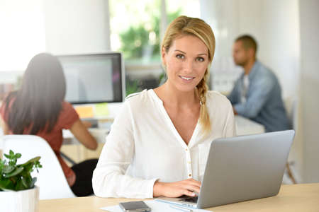 officeworker: Blond businesswoman working in office Stock Photo