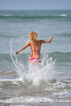 view woman: Back view of woman in bikini running into the water Stock Photo