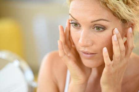 Middelbare leeftijd blonde vrouw zetten cosmetica op Stockfoto