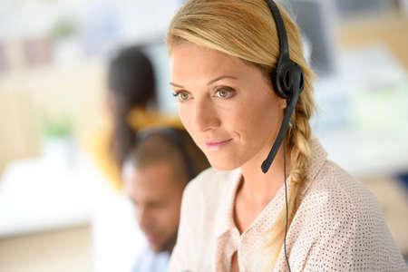 servicio al cliente: Primer plano de gerente de servicio al cliente de pie en el centro de llamadas