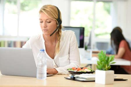 Occupato responsabile del servizio clienti di mangiare il pranzo in ufficio