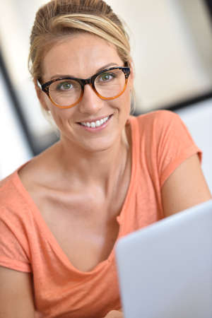 telework: Blond woman with eyeglasses working from home with laptop Stock Photo