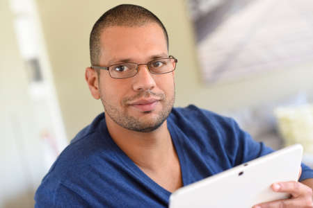 websurfing: Man with eyeglasses and blue shirt websurfing on tablet Stock Photo