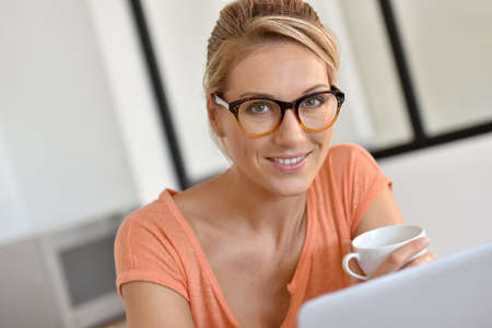 Blond woman with eyeglasses working from home with laptop Stock Photo