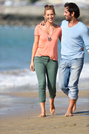 complicity: Middle-aged couple walking on the beach Stock Photo