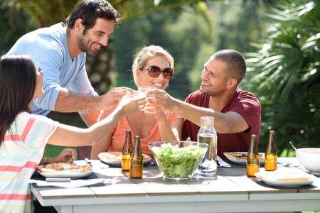 exteriores: Amigos que tienen el almuerzo al aire libre en un día soleado