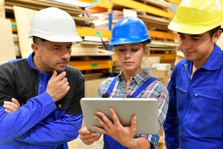 carpintero: maestro de carpintería que usa la tableta para entrenar aprendiz