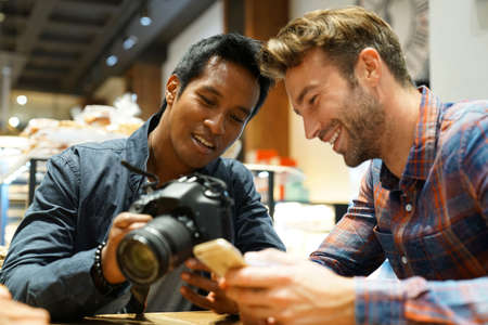 photo pictures: Guy friends in coffee shop checking pictures on photo camera