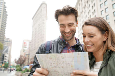 Couple in New york city looking at tourist map by Flatiron