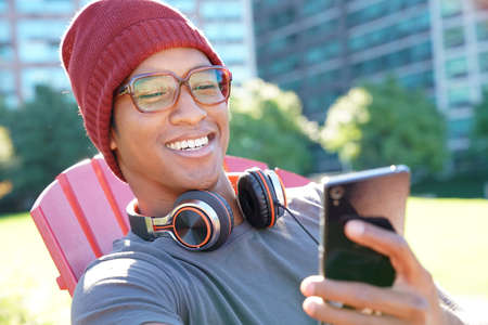 asian guy: Smiling mixed raced guy using headset outside in park