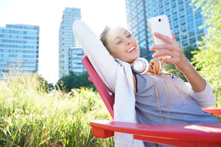 adult entertainment: Cheerful girl connected on smartphone at city park