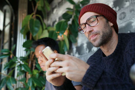 websurfing: Guy at coffee shop connected with smartphone