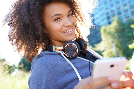 Portrait of mixed race girl in park listening to music on smartphone