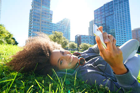 mixed race girl: Portrait of mixed race girl laying in park using smartphone Stock Photo