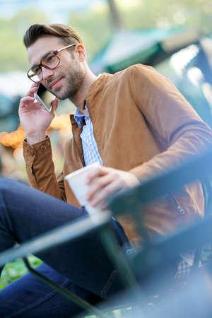Businessman talking on phone sitting in park
