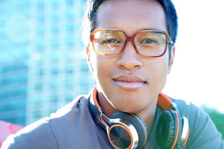 Portrait of smiling mixed raced guy with music headset outside in park