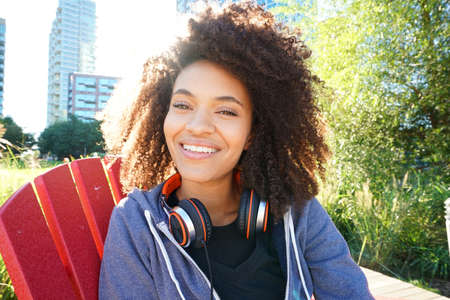 mixed race girl: Portrait of mixed race girl in park listening to music on smartphone