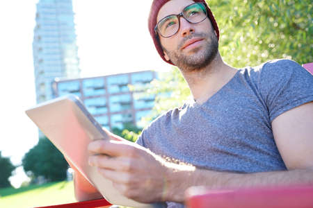websurfing: Hipster guy in park websurfing on digital tablet Stock Photo