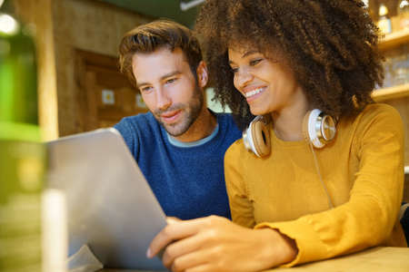 ethnic woman: Couple in restaurant connected on internet with laptop