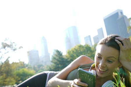 adult entertainment: Beautiful fitness girl relaxing at Central park with headset on