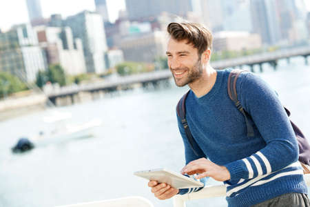 globetrotter: Man standing by the Hudson river, using digital tablet Stock Photo