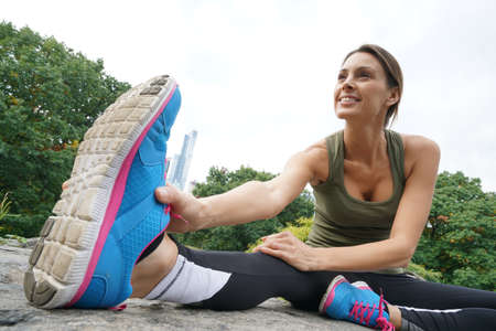 woman resting: Fitness girl doing stretching exercises at Central park Stock Photo