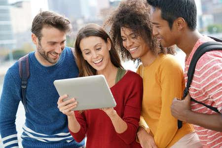 Groep vrienden in de stad van New York die tablet buiten gebruiken Stockfoto